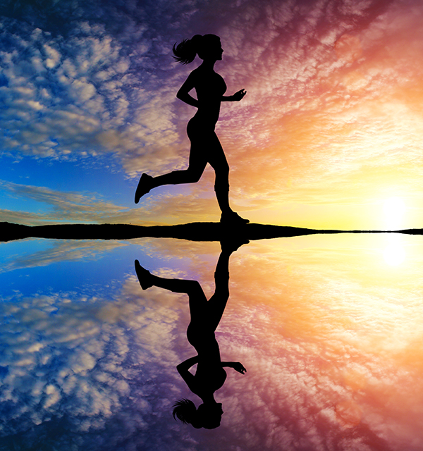Girl running at sunset with reflection in water